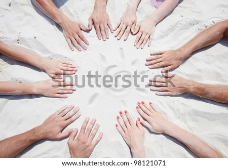 Circle of hands on sand with a sun - stock photo