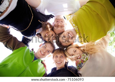 Circle of happy friends looking at camera with smiles - stock photo