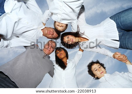 Circle of happy people over sky. - stock photo