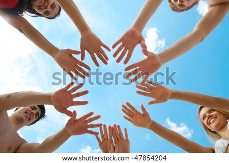 Circle of people? hands on blue sky background - stock photo