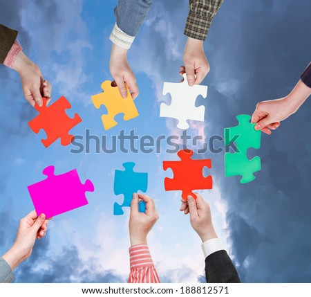 circle of people hands with different puzzle pieces with dark grey evening sky background - stock photo