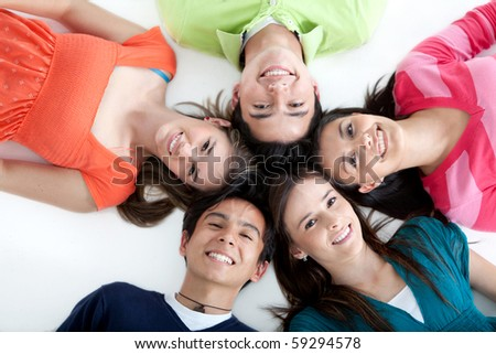 Circle of people lying on the floor and smiling - isolated over white background