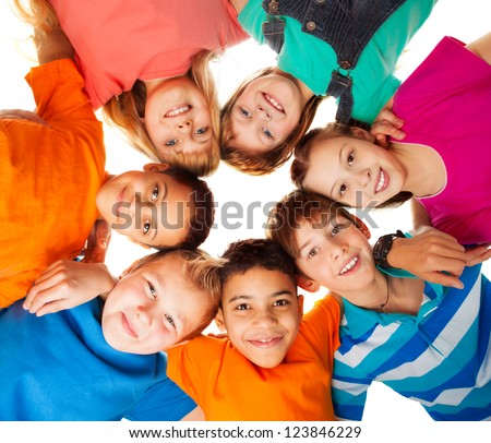 Circle of smiling positive kids looking down - diversity group of boys and girls - stock photo
