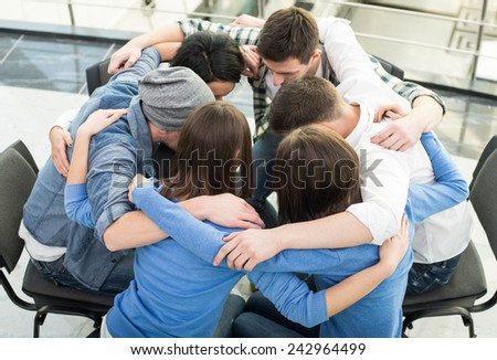 Circle of trust. Group of people are sitting embracing in circle  and supporting each other. - stock photo