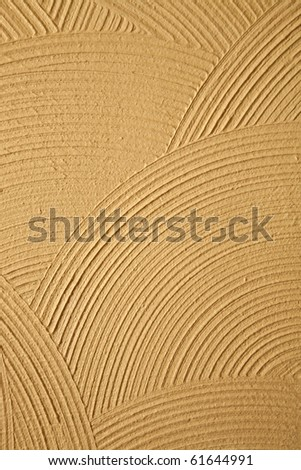 Circle patterns and texture in a yellow-gold stucco wall - stock photo
