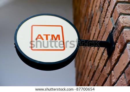 Circle shape ATM sign on brick wall - stock photo