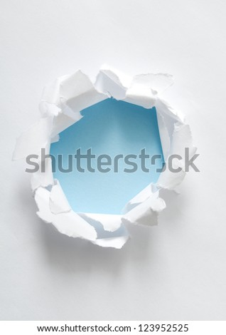 Circle shape breakthrough paper hole with white background. Focus on curled edges of paper