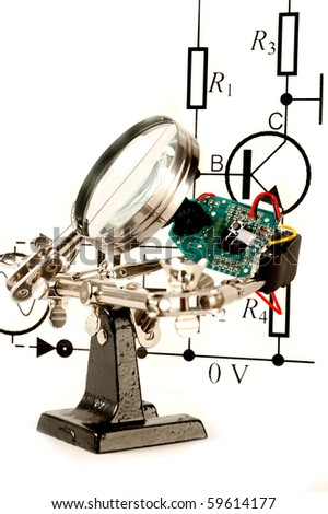 Circuit board under a magnify glass - stock photo
