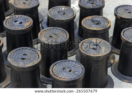 Circular cast iron water valve covers on a sidewalk. Selective focus. - stock photo