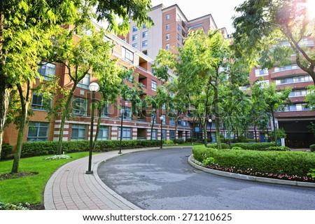 Circular driveway and sidewalk at brick condominium building - stock photo