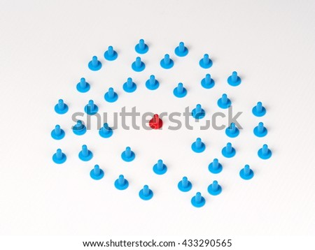 Circular group blue colored plastic hat shaped parts on white with a red one in the center - stock photo