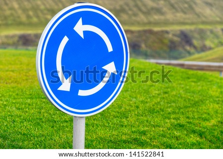 Circular junction road sign in blue - stock photo
