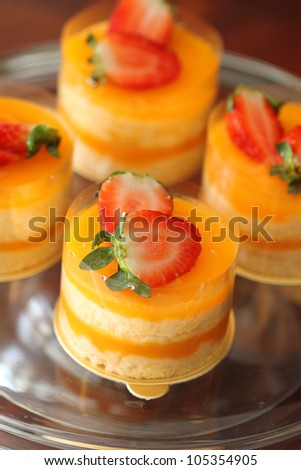 circular orange cakes with two pieces of strawberry