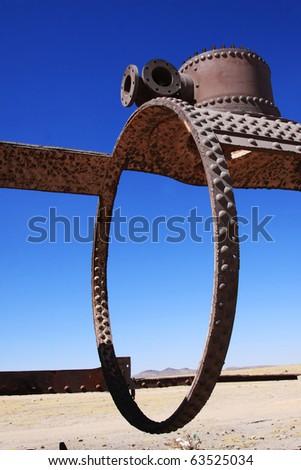 circular piece of an old train in uyuni desert in bolivia - stock photo