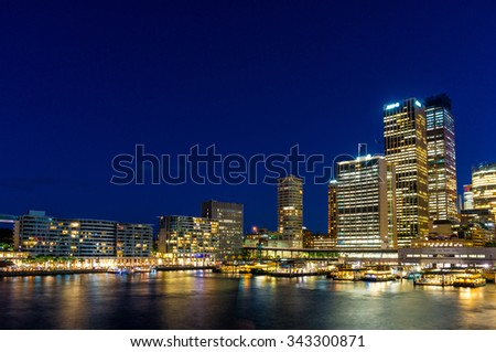 Circular Quay,  Sydney Business District Centre, train and ferry station at night, with illuminated skyscrapers and ferries. Sydney, Australia. Long exposure