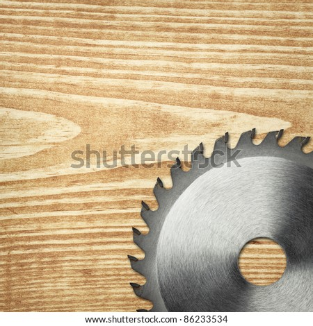 Circular saw blade on a wood board. - stock photo
