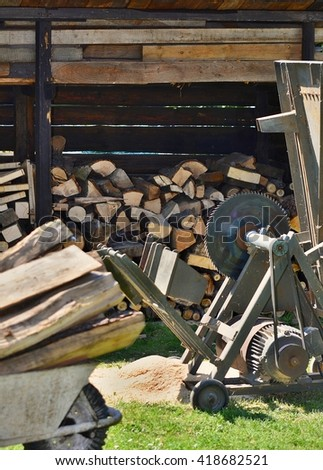 Circular saw with wood logs and log store in garden.