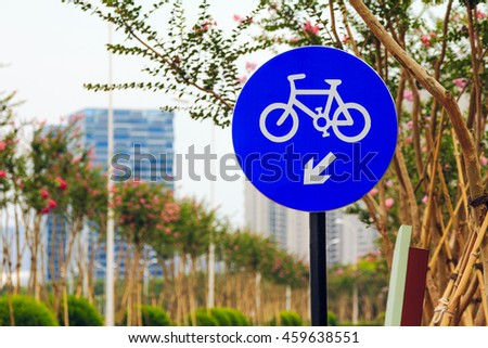Circular shape blue road sign with white bicycle, placed next to the road, showing where bikes should go. Along a long streets are deployment beautiful trees.