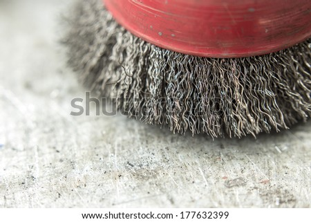 circular wire brush on workbench close up - stock photo