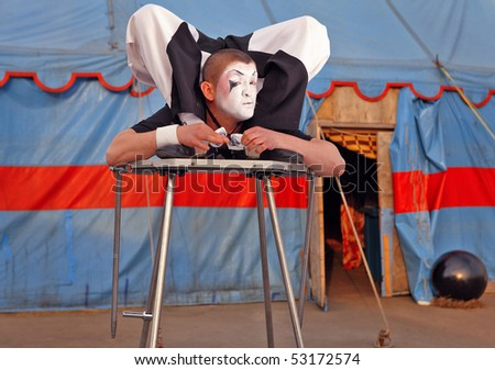 Circus acrobat with a plastic body executes his  tricks. Photo. - stock photo