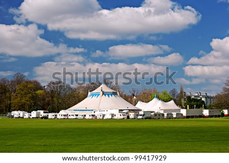 Circus big top tents surrounded by caravans in rural park