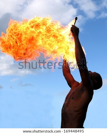 Circus fire-eater blowing a large flame from his mouth - stock photo