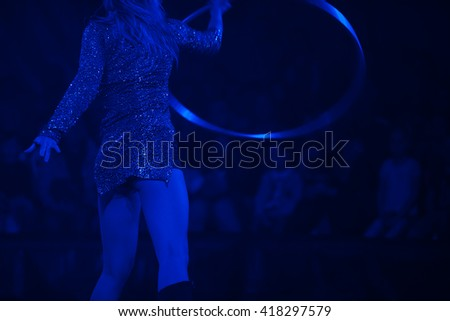 Circus performance concept. Dancing woman rotates hula hoop in show watchers background. Blue circus illumination. Indoor shot - stock photo