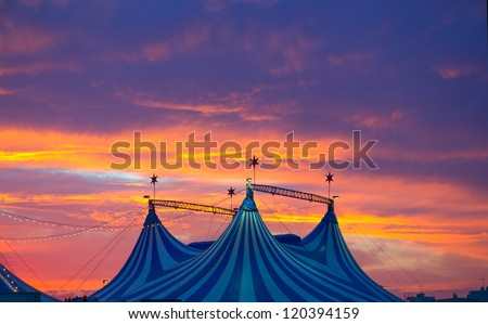 Circus tent in a dramatic sunset sky colorful orange blue with lights - stock photo