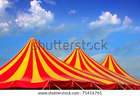 Circus tent red orange and yellow stripped pattern blue sky - stock photo