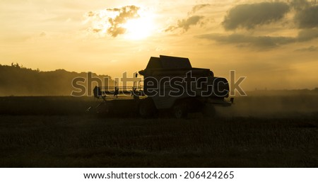 Cirencester, Gloucestershire, July 17th 2014 - Massey Ferguson Combine Harvester working the field at night - During Sunset  - stock photo