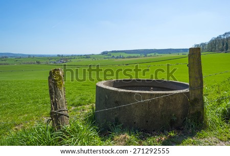 Cistern with water in a sunny meadwo in spring - stock photo