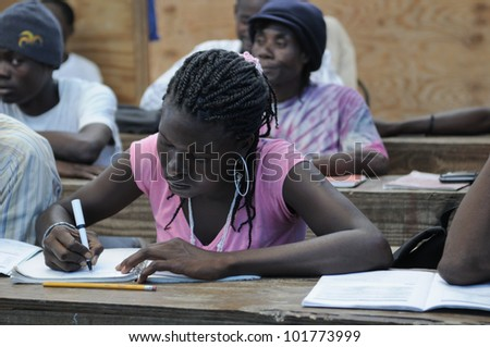 CITE SOLEIL- AUGUST 25:  A female student taking notes in a local community school in Cite Soleil- one of the poorest area in the Western Hemisphere on August 25 2010 in Cite Soleil, Haiti. - stock photo