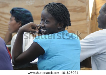 CITE SOLEIL- AUGUST 25: An Haitian teen sharing a smile in a local community school in Cite Soleil- one of the poorest area in the Western Hemisphere on August 25 2010 in Cite Soleil, Haiti. - stock photo