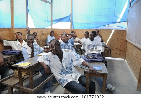 CITE SOLEIL-AUGUST 25:Students laughing at a joke by their teacher in a local community school in Cite Soleil-one of the poorest area in the Western Hemisphere on August 25 2010 in Cite Soleil, Haiti. - stock photo