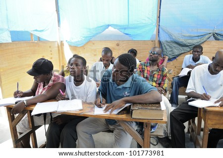 CITE SOLEIL-AUGUST 25: Students taking notes in a basic english class in a  community school in Cite Soleil- one of the poorest area in the Western Hemisphere on August 25 2010 in Cite Soleil, Haiti. - stock photo
