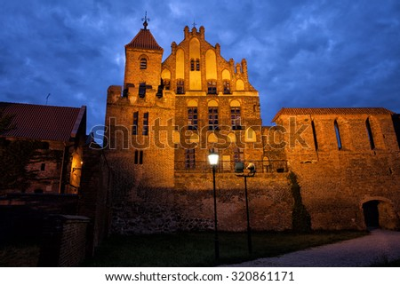 Citizen Court by night, sentry tower and city wall in Torun, Poland, former summer residence of the Brotherhood of St. George, medieval Gothic architecture from 13-15th century.