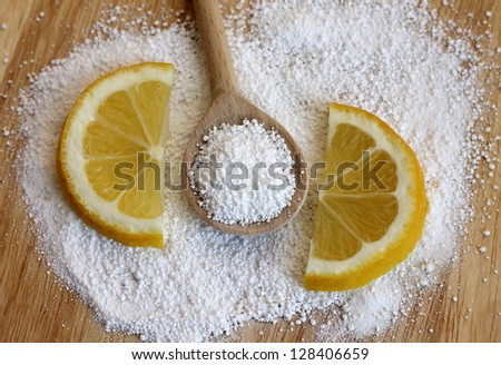 citric acid in wooden spoon with lemon, close-up - stock photo