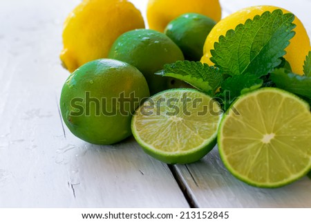 Citrus fresh fruits - lemon and lime on the white wooden table - stock photo