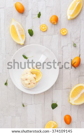 Citrus fruit mousse. Homemade lemon almond mousse with candied kumquats  peel.  Top view, blank space, rustic background