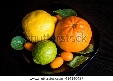 Citrus fruit on black background. Ingredients for fruit salad. Close-up - stock photo
