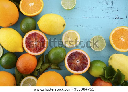 Citrus Fruit on vintage aqua distressed wood table, including navel and blood oranges, lemons and limes.   - stock photo