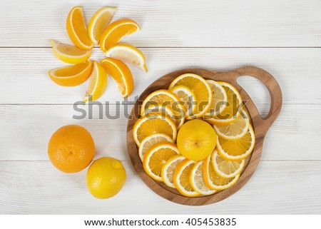 Citrus fruit slices arranged into revolving shape and decorated on a cutting board in top view. - stock photo