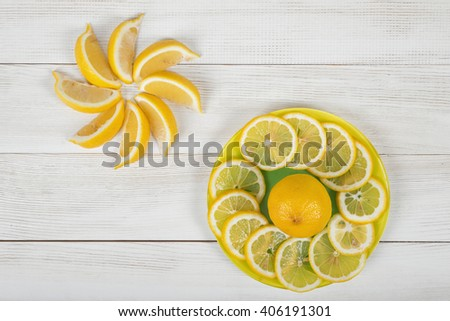 Citrus fruit slices arranged into revolving shape and decorated on a plate in top view. - stock photo