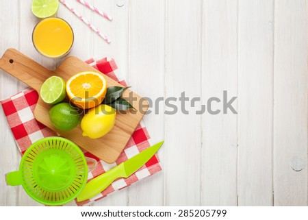 Citrus fruits and glass of juice. Oranges, limes and lemons. Over white wood table background with copy space - stock photo