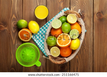 Citrus fruits and glass of juice. Oranges, limes and lemons. Top view over wood table background  - stock photo
