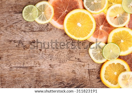 Citrus fruits cut background- oranges, lemons, limes, grapefruit on a wooden background