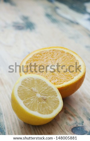 Citrus fruits. Half-cut fresh juicy orange and lemon on rustic wooden table. Shot at daylight, shallow depth of field. - stock photo