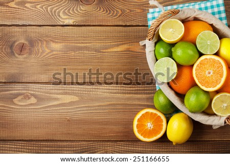Citrus fruits in basket. Oranges, limes and lemons. Top view over wooden table background with copy space  - stock photo