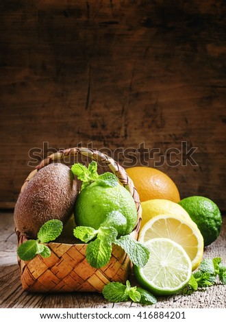 Citrus fruits, kiwi and mint leaves in a wicker basket, vintage wooden background, selective focus - stock photo