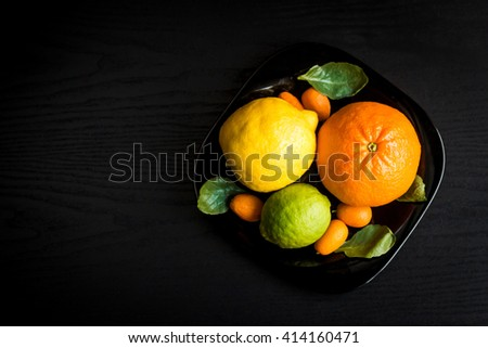 Citrus fruits on black background. Orange, lemon, lime, kumquat. Ingredients for citrus salad. Top view - stock photo